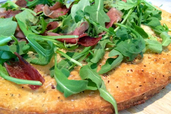 Pizza with prosciutto, arugula and balsamic drizzle